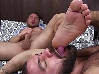 Hunk relaxes and masturbates while having his bare feet worshiped