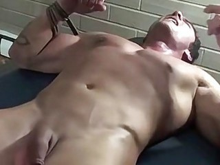 Muscular gay guy stripped naked to have his body teased