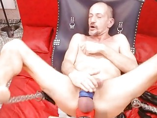 Old fuck bounces his ass on a giant red dildo