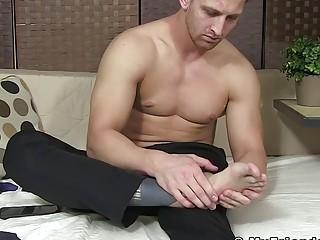 Handsome businessman massages his feet